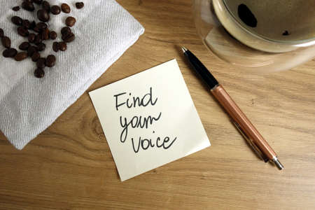 Find your voice text handwritten on sticky note with coffee and pen, communication, brand or identity concept