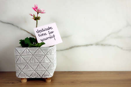 Slogan dedicate time for yourself handwritten on sticky note with blossoming flower, self care concept