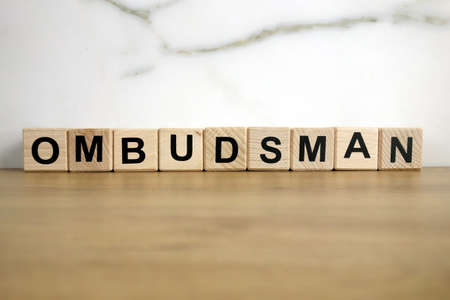 Ombudsman word from wooden blocks on desk, public administration concept
