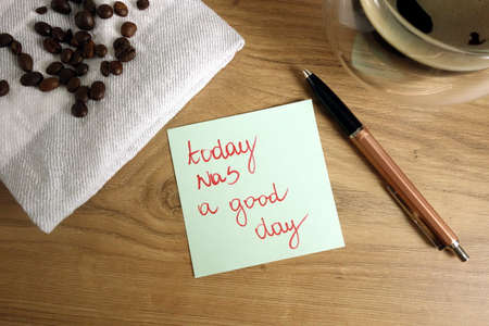 Today was a good day text handwritten on sticky note with coffee and pen, personal development and positivity concept 免版税图像