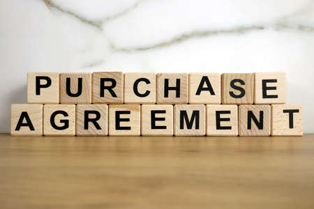 Purchase agreement text from wooden blocks, financial concept