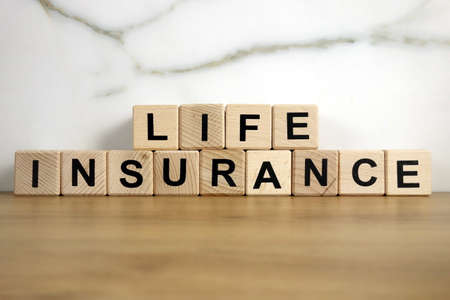 Life insurance text from wooden blocks, financial concept