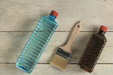 A brush lies next to plastic bottles with stain and solvent on an old white vintage wooden plank table.
