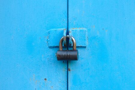 metal blue door with padlock. Old garage gates with keyhole