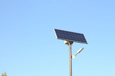 street lamp with a solar battery against a blue sky Stock Photo