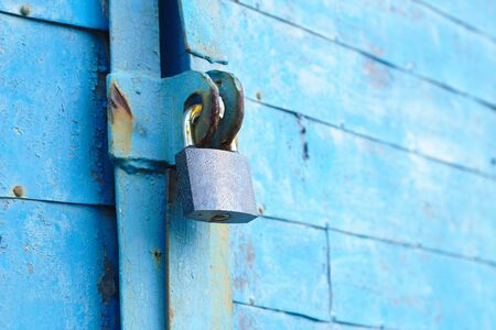 old padlock on a blue metal door with wooden planks cracked paint and rust Фото со стока