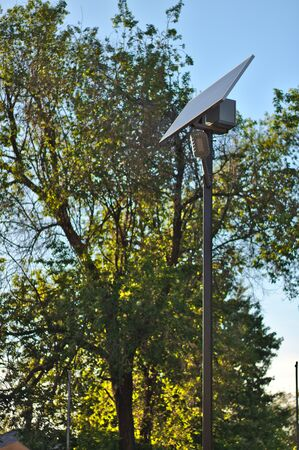 street lamp with a solar battery against a blue sky and trees Stock Photo
