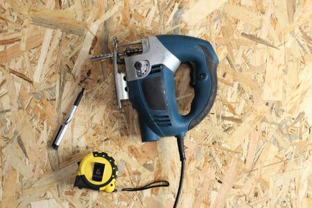 jigsaw, tape measure and pencil on osb plywood