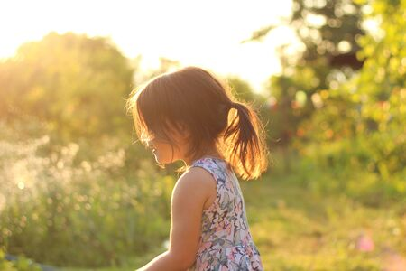 silhouette of a little girl with a ponytail in a flower dress outdoors in the rays of sunny sunset