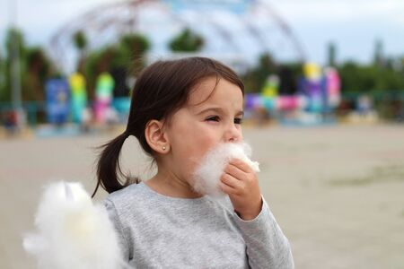Little funny white girl with tails with narrow eyes holds cotton candy with his lips while walking outdoors