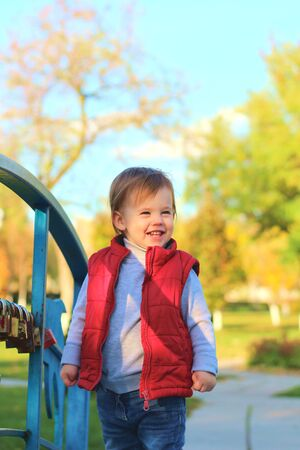 white blond kid in a red waistcoat considering padlocks on the railing of the bridge over the river. Walk in the autumn park 写真素材 - 136085020