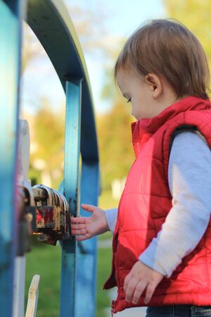 white blond kid in a red waistcoat considering padlocks on the railing of the bridge over the river. Walk in the autumn park 写真素材 - 136085033