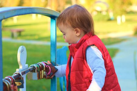 white blond kid in a red waistcoat considering padlocks on the railing of the bridge over the river. Walk in the autumn park 写真素材 - 133561975