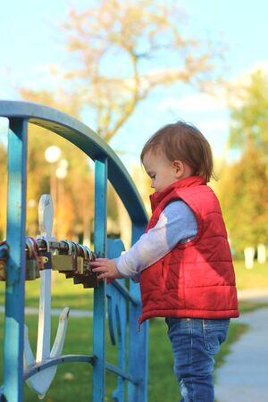 white blond kid in a red waistcoat considering padlocks on the railing of the bridge over the river. Walk in the autumn park 写真素材 - 133561985