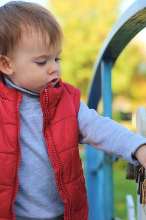 white blond kid in a red waistcoat considering padlocks on the railing of the bridge over the river. Walk in the autumn park 写真素材 - 133562235