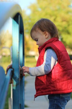 white blond kid in a red waistcoat considering padlocks on the railing of the bridge over the river. Walk in the autumn park