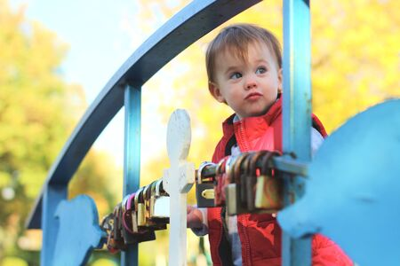 white blond kid in a red waistcoat considering padlocks on the railing of the bridge over the river. Walk in the autumn park 写真素材 - 133562432