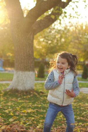 A merry child scatters an armful of yellow fallen leaves. Sunny sunset in autumn park outdoors 写真素材 - 133549858