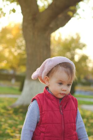 A small child in a fluffy pink hat and red vest is running in the autumn park. Beautiful fall sunny day outdoors. 写真素材 - 133549860