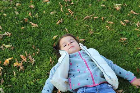 little girl lying on green grass and looking at the sky. Snow angel on the lawn with fallen leaves. 写真素材 - 133549936