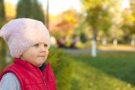 A small child in a fluffy pink hat and red vest is standing near a pine in the autumn park. Beautiful fall sunny day outdoors.