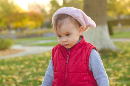 A small child in a fluffy pink hat and red vest is running in the autumn park. Beautiful fall sunny day outdoors. 写真素材 - 133550534