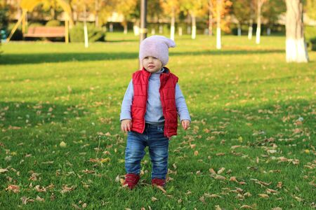A small child in a fluffy pink hat and red vest is running in the autumn park. Beautiful fall sunny day outdoors. 写真素材