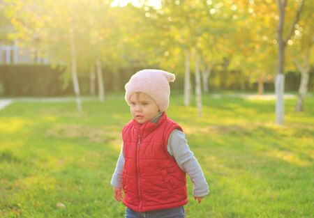 A merry child scatters an armful of yellow fallen leaves. Sunny sunset in autumn park outdoors 写真素材 - 133550684