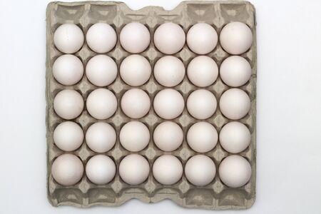 An isolated tray of eggs from recycled materials with 30 white eggs on a white background. Top view