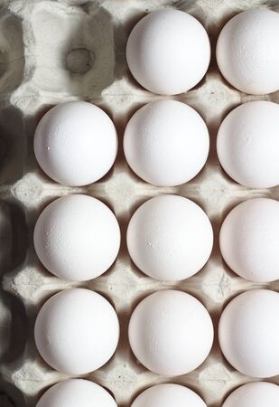 An isolated tray of eggs from recycled materials with white eggs on a white background. Top view 写真素材