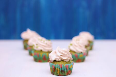 A row of spinach-mint cupcakes with fruit jam and berry cream on top 写真素材