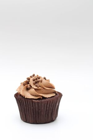 Isolated chocolate cupcake with cream top and crispy topping on a white background