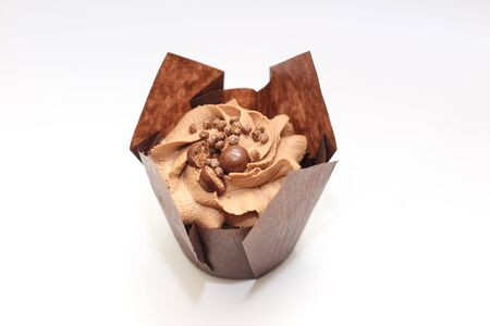 Isolated chocolate cupcake with cream top and crispy topping in paper on a white background