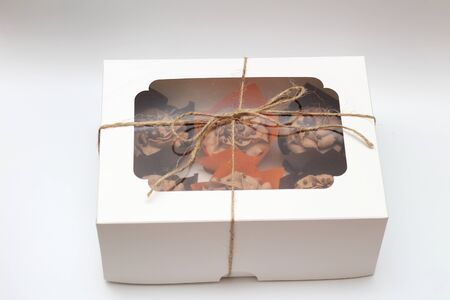 box tied with a rope with a transparent lid with chocolate cupcakes with cream top and crispy topping in paper on a white background 写真素材