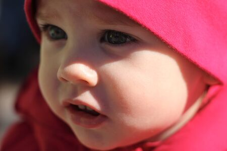 Portrait of a beautiful white baby in a red hat
