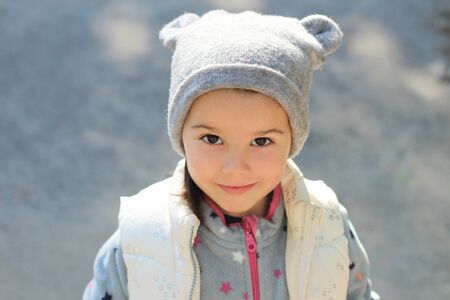 Cheerful smiling white child in a hat with ears and a vest looks up