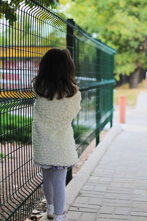 A little girl with long dark hair in a fluffy white coat turned away near the metal fence. Blurred back street background 写真素材