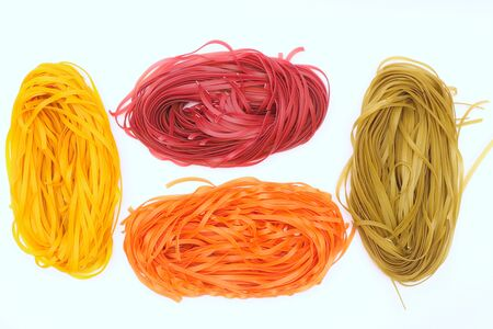 Isolated colored spaghetti nests on a white background. Top view