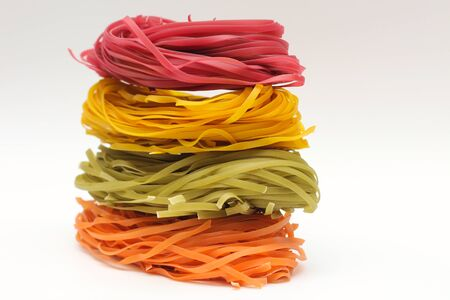Isolated colored spaghetti nests on a white background. 写真素材