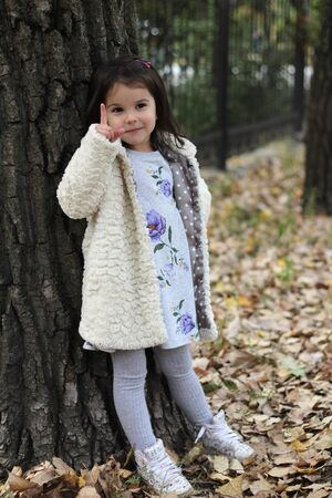 A little girl with long dark hair in a fluffy white coat and colorful dress is standing in front of a big tree. Blurred park background 写真素材