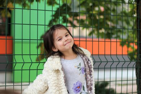 A little girl with long dark hair in a fluffy white coat stands in front of a metal fence. Blurred back street background 写真素材