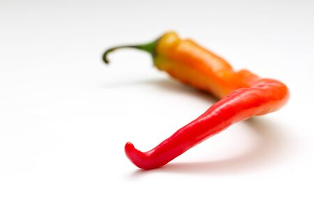 isolated red and yellow chili peppers on a white background.