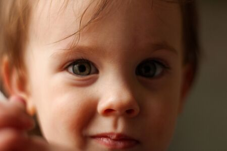 Close-up portrait of a little cute white baby with a dirty face in soft light and blurry background Stock Photo