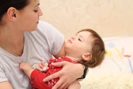 White smiling dark-haired girl in a casual T-shirt holds in her arms a small cute child in red clothes