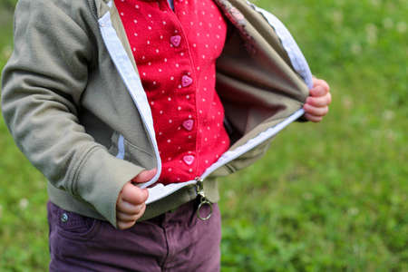 Little children's handles unzip zip on a jacket on a background of blurred green grass Stock Photo