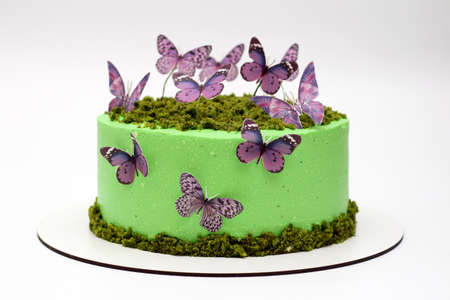 Beautiful tasty green cake with butterflies on a white background Фото со стока