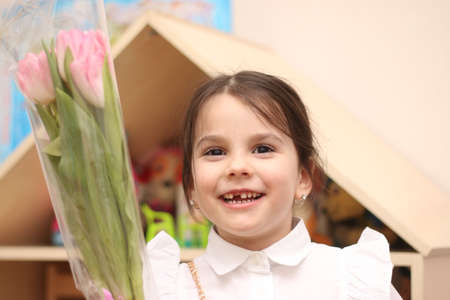 Little girl with a bouquet of pink tulips on the background of a dollhouse smiling toothlessly looking at the camera