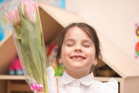 Little girl with a bouquet of pink tulips on the background of toothless smiling looking at the camera