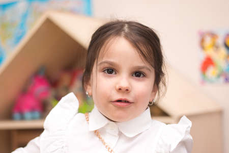 Little girl in a white shirt on the background of a dollhouse smiling toothlessly looking at the camera