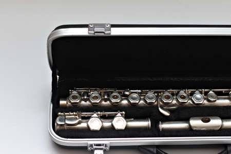 Partial view of shiny disassembled silver flute in black case against white background